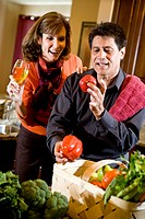 Mature couple in kitchen drinking white wine and looking at fresh vegetables