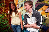 Teenagers standing by mural