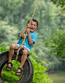 A boy plays on a tire swing.