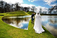 Newlywed couple walking on grassy bridge
