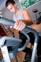 Young man using the crosstrainer at gym,