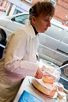 Shop Assistant cutting Polish cheese cake for customer in Polish Delicatessen,