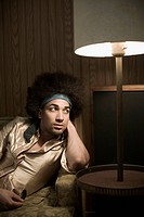 Man with Afro next to Lamp