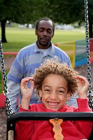 Man pushing boy on a swing