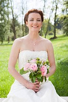 Smiling bride with bouquet on wall