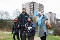 Asian family walking near tower blocks