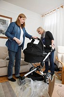 Mother with pregnant daughter looking at new pram