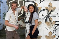 Couple leaning against graffiti covered wall