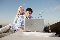 Man and woman looking at laptop computer outdoors