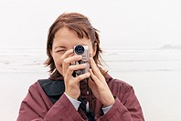 Woman using video camera at beach
