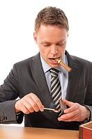 Junger Geschäftsmann in Anzug und Krawatte sitzt am Schreibtisch und genießt eine gute Zigarre aus seinem Humidor. Freigestellt vor weißem Hintergrund