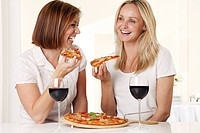Two Women Eating Pizza With Red Wine