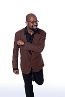 Studio portrait of mature happy African American man in brown blazer dancing standing on one leg on white background