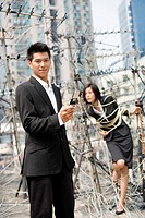 Businessman with a Cell Phone and Businesswoman Tied Up