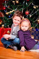 Zwei Kinder in der Nähe von Weihnachtsbaum