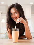 Mixed race woman drinking smoothie