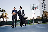 Businessmen walking on basketball court