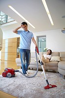 Woman On Couch Listening Music And Man Vacuuming