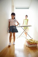 Girl Standing In Front Of Woman Ironing