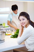 Portrait Of Woman And Man In Background In Kitchen