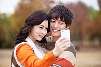 Couple Taking Pictures With Phone In Autumn