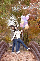 Young Couple On Foot Bridge Holding Balloon In Autumn