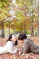 Young Couple Lying On Leaves In Autumn