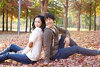 Young Couple Sitting On Leaves In Autumn