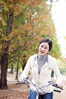 Young Woman Cycling In Autumn