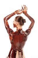 Attraktive junge Frau deren Rücken völlig mit leckerer, brauner Schokoladensauce bedeckt ist macht eine entspannte Pose mit dem Rücken zur Kamera und ...