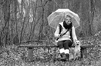 Young woman with umbrella and dog