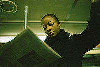 Businesswoman Reading Newspaper While Riding Subway