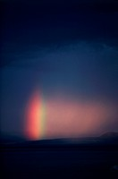A rainbow breaks through storm clouds and rain over Mono Lake.