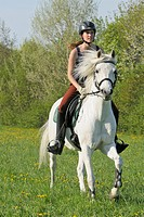 Young rider on a German Riding Pony galloping on a meadow in spring