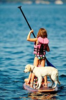 young girl on lake paddleing stand up paddle boards