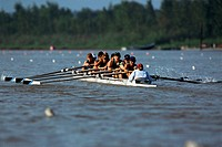 A women´s rowing team races their shell on a river.