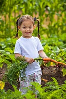 Young girl with freshly picked carrot at organic farm, Quadra Island, BC, Canada