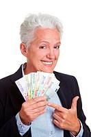 Seniorin hält Geldfächer aus Euroscheinen
