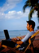 Man Using Laptop near Beach