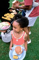 Girl with plate of food at barbeque picnic