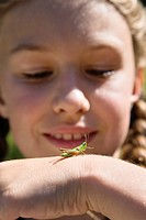 Girl 8 years with grasshopper on hand, Bavaria, Germany