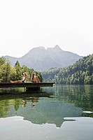 Two teenage girls sitting on a jetta at lake Schwansee, Schwangau, Allgaeu, Bavaria, Germany