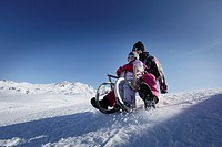 Two girls, 12 and 2 years, sledging down a hill on a tobogan, sledge, Kloesterle, Arlberg, Austria