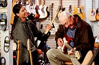 Senior man playing guitar with young salesman
