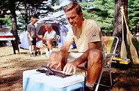 Man using his PDA with a keyboard while camping