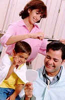 Woman giving husband and son haircuts
