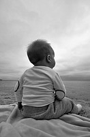 Baby Boy Sitting on Beach, Rear View