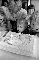 Young Boy Blowing out Birthday Cake Candles as Other Children Watch