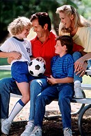 Family with soccer ball sitting on picnic table