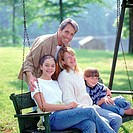 Portrait of a family sitting on a swing